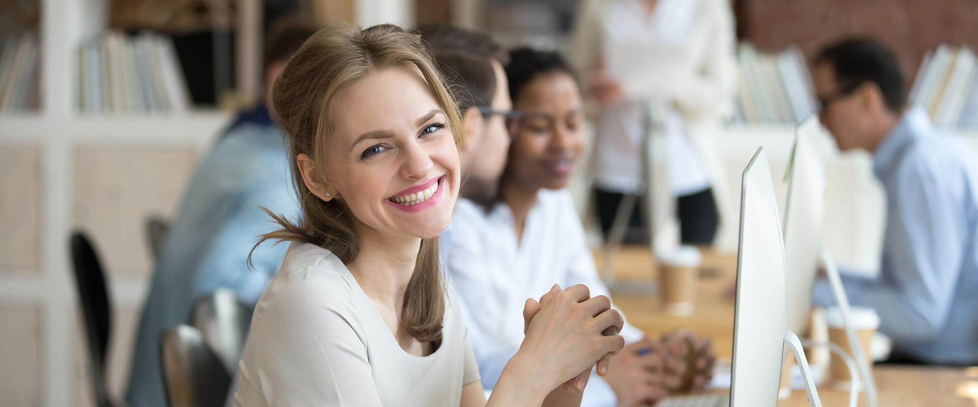 Eine Frau nimmt mit anderen Teilnehmer an einer Weiterbildung teil, Blick in die Kamera.