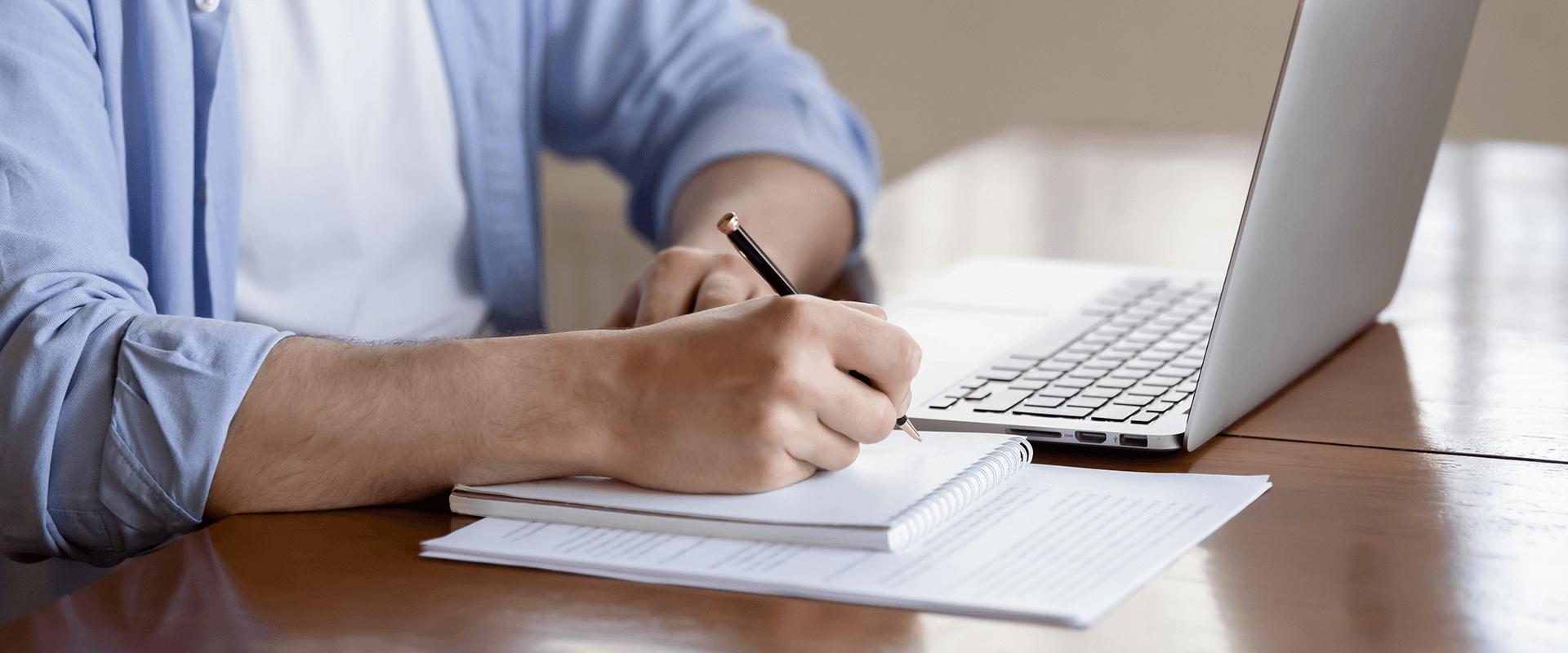 Nahaufnahme - Ein Mann macht sich Notizen beim Online-Seminar.