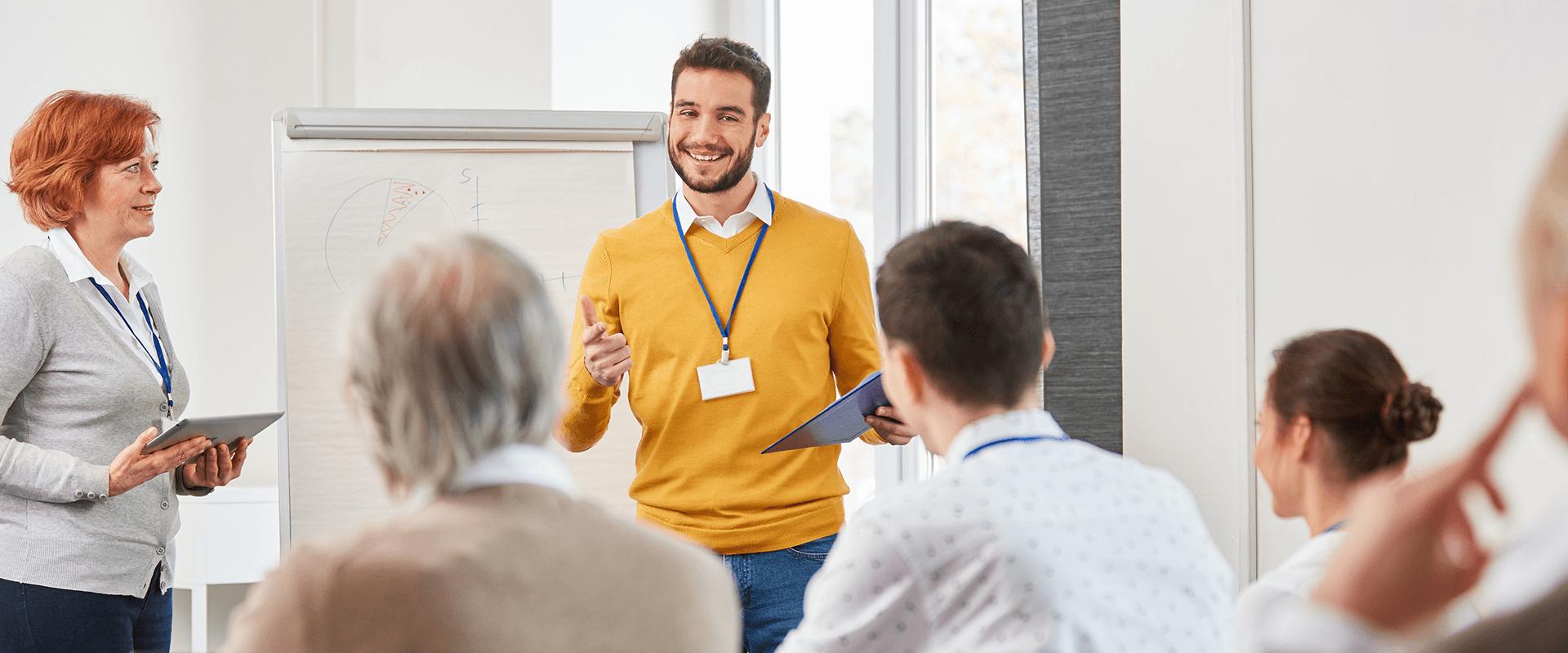 Mehrere Personen im Seminarraum, ein Mann steht vor dem Flipchart und führt eine Diskussion mit weiteren Teilnehmern.