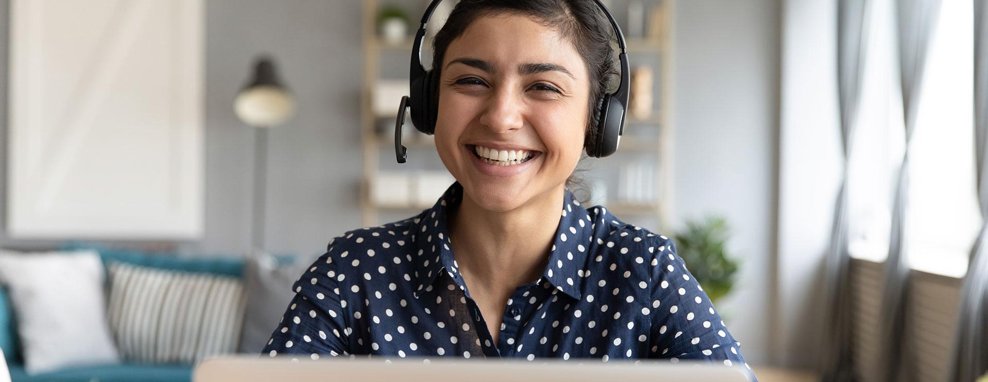 Frau mit Headset vor einem Notebook