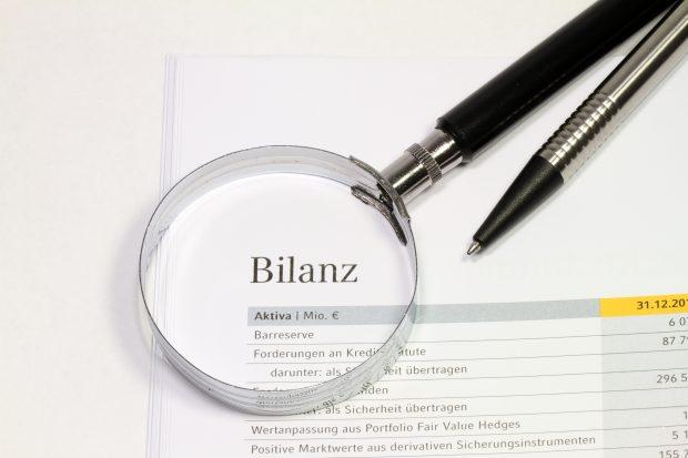 Lupe und ein Kugelschreiber auf einem Blatt Papier mit der Überschrift Bilanz
