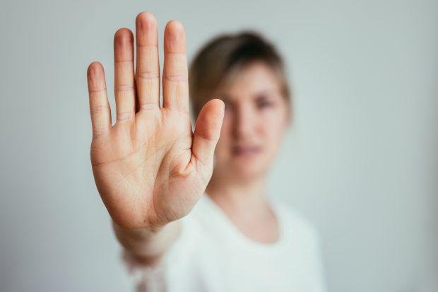 Eine Frau zeigt eine Stop-Geste mit einer Nahaufnahme auf die Handfläche