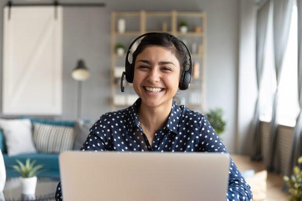 Junge Frau mit Kopfhörern sitzt vor einem Notebook